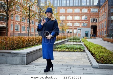 Blonde woman in blue suit and hat walks in inner yard of house of red brick.