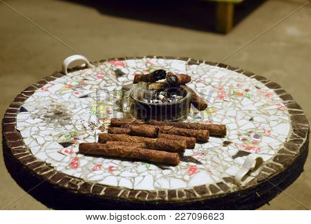 Cigar And Ashtray On The Table Of The Glued Pieces Of Pottery. Homemade Cigars From Leafy Tobacco Le