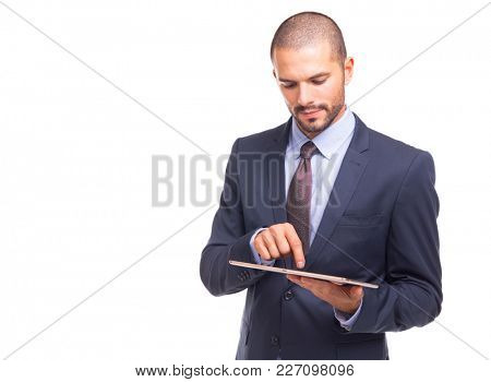 Confident handsome businessman working on digital tablet, isolated on a white background