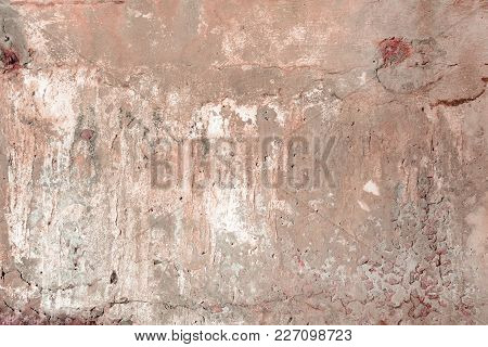 Red Concrete Wall With Cracks And Holes. Background With An Unusual Texture.
