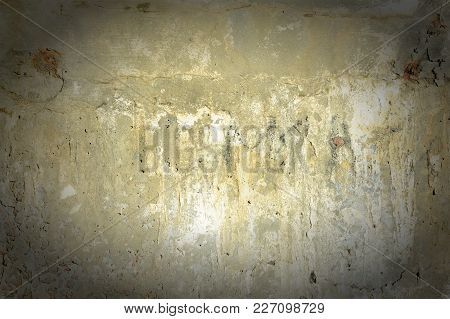 Yellow Concrete Wall With Cracks And Spots. Background With Unusual Texture And Vignette.