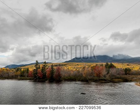 Penobscot River Calmly Flows Below A Cloudy Mount Katahdin In Autumn