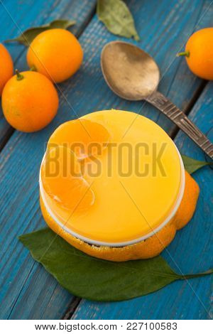 A Sweet Orange Jelly Pudding With Cumquats And Tangerine Lobes With Green Leaves On Blue Rustic Wood