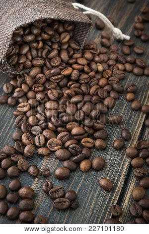 A Bag Of Roasted Arabica Coffee Beans On A Dark Wooden Background Closeup