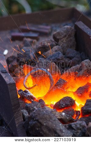 Blacksmith Furnace With Burning Coals, Tools, And Glowing Hot Metal Workpieces, Close-up
