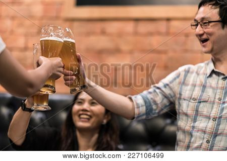 Group Of Happy Asian Friends Cheering, Clinking Or Toasting Beer Glasses At Restaurant Pub Or Bar. H