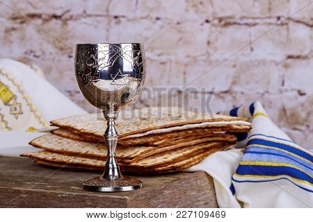 Jewish Holidays: Passover Pesach Matzah And A Silver Cup Full Of Wine With A Traditional Blessing