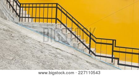 Tiled Stairs And Steel Railing With Yellow Concrete Wall