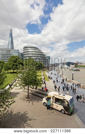London, UK - 7th June 2017: Southbank walkway with ice cream van and tourists on the promenade and the City Hall, The Shard and the river Thames beyond.