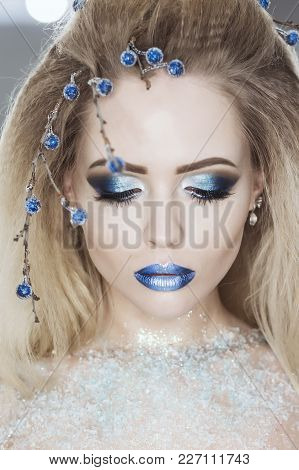 Winter Beauty Woman. Christmas Girl Makeup. Holiday Make-up. Snow Queen High Fashion Portrait Over B