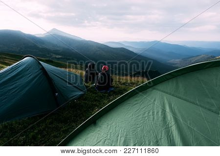 Couple near tent on mountains closeup. View of the stony hills glowing by evening sunlight. Dramatic autumn scene, Carpathian mountains. Landscape photography