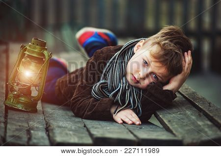 Portrait Of A Boy With A Kerosene Lamp .stylish Boy Holding An Old Lamp