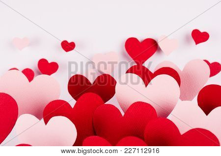 Valentine Day Background. Stream Of Fly Out Red And Pink Paper Hearts On White Color Backdrop.