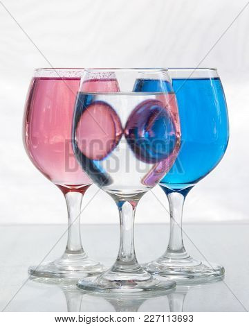 Three Glasses Of Water Showing Reflections. Also Distortion And Refraction Of Light And Alternating