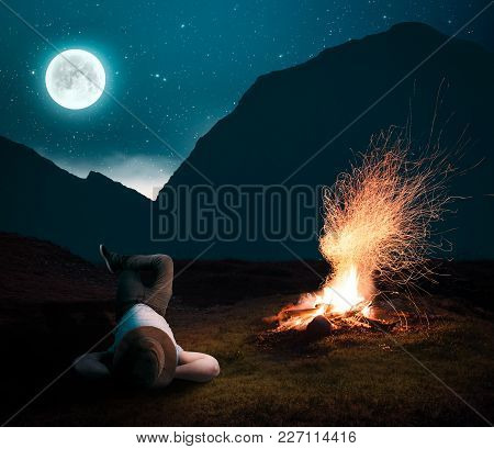 Man Relaxing Next To The Fire Camp Into The Night, Admiring The Stars.