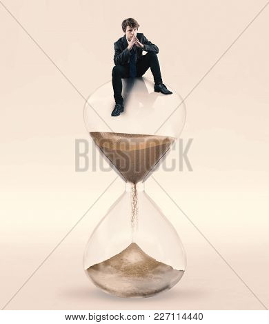 Thoughtful Businessman Sitting On Top Of A Hourglass. Concept Of Taking A Decision Until The Deadlin