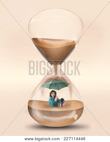 Girl With An Umbrella Inside A Hourglass. Concept Of Time Pressure .