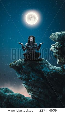 Woman Meditates On Top Of A Rock Into The Night.