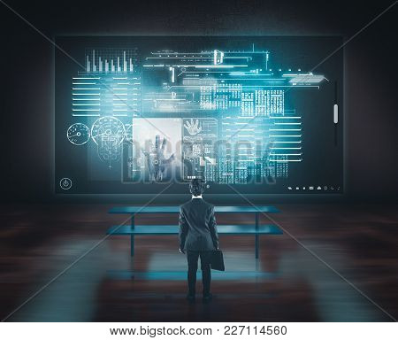 Businessman Watching Big Touch Screen Above The Desk.