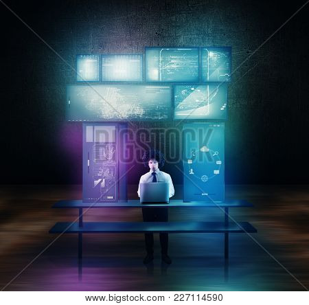 Businessman Using His Laptop Surrounded By Tocuh Screens At His Desk.