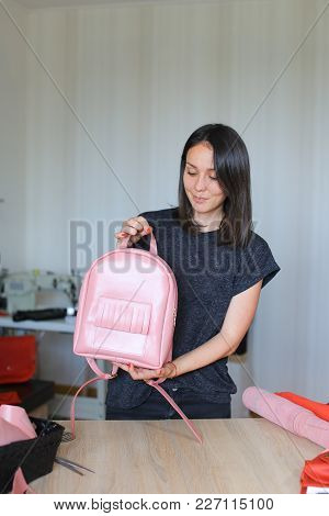 Seamstress Took Part In Competition And Won Pink Leather Backpack And Purse. Happy Young Woman Stand