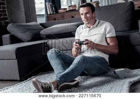 Favorite Leisure Activity. Focused Gentleman In Casual Sitting On The Floor And Focusing His Attenti