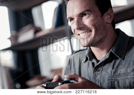 Ready To Win. Excited Mature Gentleman Grinning Broadly While Holding A Console Controller And Playi