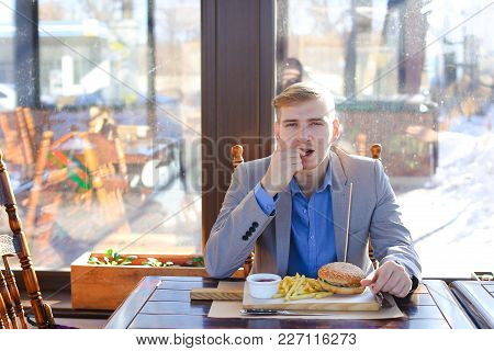 Businessman Enjoying Eating Hamburger And French Fries With Sauce. Young Man Wears Grey Jacket With