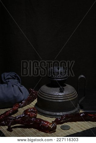 Old Kerosene Lamp Red Hot Pepper And Bag With Beans On A Dark Background