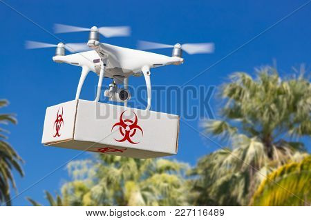 Unmanned Aircraft System (UAV) Quadcopter Drone Carrying Package With Biohazard Symbol Label Over Tropical Terrain.