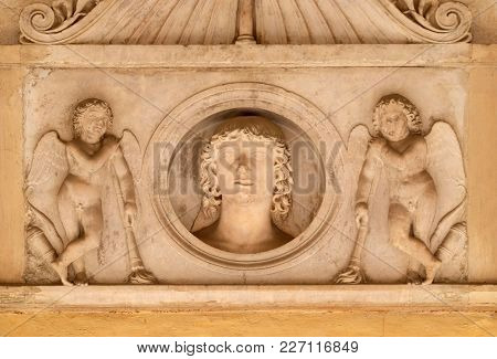 ROME, ITALY - SEPTEMBER 03: Young man of the Colonna family, flanked by a pair of cupids with downturned torches, relief in portico of church dei Santi XII Apostoli in Rome, on September 03, 2016.