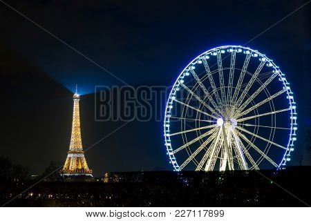 PARIS, FRANCE - CIRCA DECEMBER 2016: The Eiffel Tower and the Roue De Paris (Paris ferris wheel) at night.