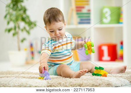 Happy Child Playing With Colorful Plastic Bricks On The Floor. Toddler Having Fun And Building A Tra