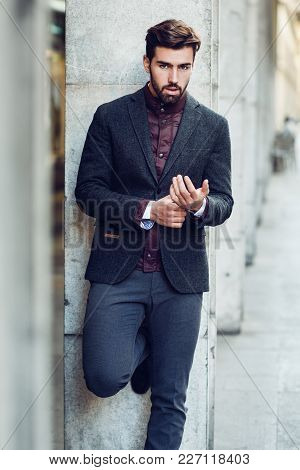 Young Bearded Man In Urban Background Wearing British Elegant Suit In The Street.