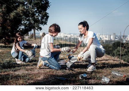 Our Environment. Nice Pleasant Smart Children Sitting And Collecting Garbage While Helping The Envir