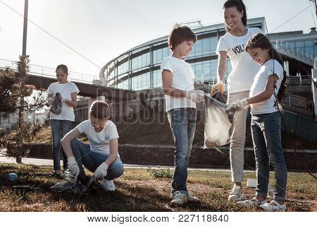 Ecological Project. Cute Positive Smart Children Holding A Litter Bag And Smiling While Participatin