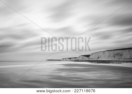 Stunning Black And White Long Exposure Landscape Image Of Low Tide Beach With Rocks At Sunrise