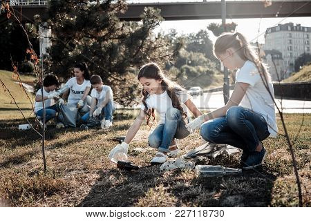 Sustainable Lifestyle. Joyful Positive Smart Children Smiling And Cleaning Garbage While Taking Part