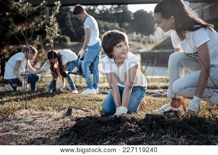 Young Environmentalist. Cheerful Nice Positive Woman Looking At The Boy And Smiling While Helping Hi