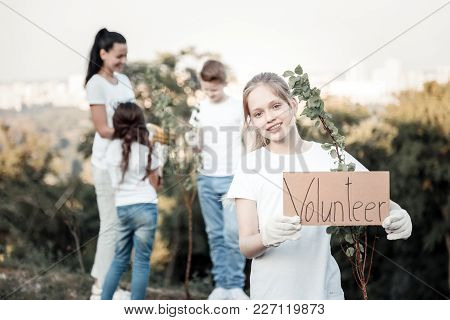 I Want To Help. Joyful Nice Pleasant Girl Standing Near The Young Tree And Looking At You While Hold