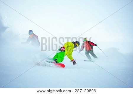 Skiers And Snowboarers Downhill At Ski Slope In Cloud Of Powder. Ski Resort Concept