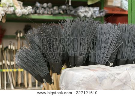 Brooms For Sale At A Hardware Store.