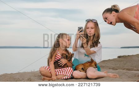 Two Teenage Are Sitting On A Sandy Beach. Near Them Is The Mother Of The Girls. The Sisters Show The