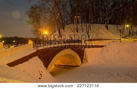 Winter Evening In The Park. Bridge Over The Lake. Evening Lighting.