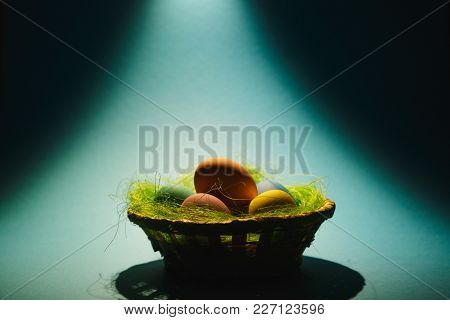 Colorful Pastel Monophonic Traditional Painted Easter Eggs In Basket With Green Grass On Blue Yellow