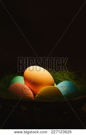 Colorful Pastel Monophonic Traditional Painted Easter Eggs In Basket With Green Grass On Dark Yellow