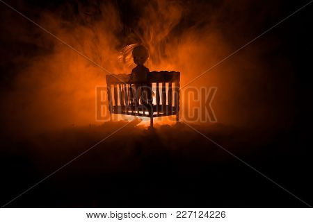 Old Creepy Eerie Wooden Baby Crib In Dark Toned Foggy Background. Horror Concept. Scary Baby And Bed