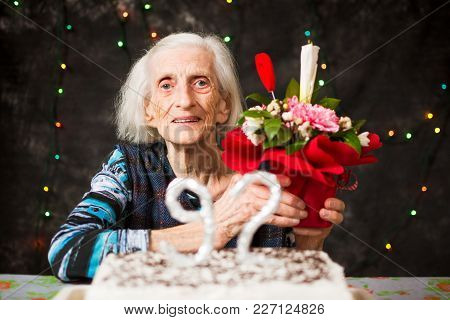 Senior Woman Holding A  Present On Birthday Celebration