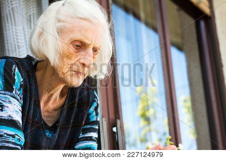 Senior Woman Looking Out Of Home Window Alone