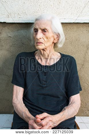 Portrait Of Ninety Years Old Grandma Sitting Outdoors